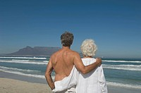 Rear view of senior woman and senior man, standing arm in arm on beach, looking at Table Mountain. Table View, Cape Town, Western Cape Province, South...