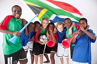 A group of young mixed race boys in soccer supporters kit with South African flags and vuvuzelas, South Africa