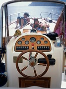 The helm of a boat and people sunbathing on deck
