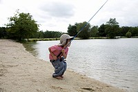 A boy fishing at the edge of a lake