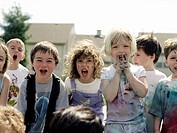 A medium group of children in paint splattered clothes yelling at the camera