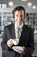 A man wearing a telephone headset and holding a cup of coffee
