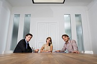 Three people sitting at a table in a conference room