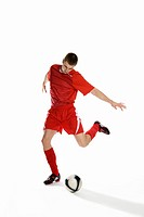 Studio shot of a soccer player kicking a soccer ball