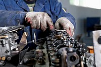 A mechanic fixing an engine