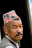 Portrait of a Nepali man wearing a traditional Nepali hat.