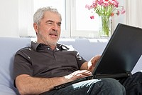 A senior man using a laptop