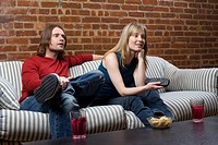 A young couple sitting on a sofa with a remote control