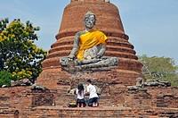 Gebet vor einer verwitterten Buddhastatue mit Erdberührungsgeste Bhumisparsa mudra, und Chedi des Wat Worachetha Ram, Ayutthaya, Thailand, Asien