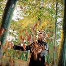 A woman throwing autumn leaves.