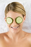 Smiling young woman lying on towel with cucumber slices over eyes (thumbnail)