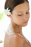 Portrait of young woman with flower in her hair and exfoliating scrub on her back