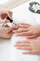 Woman getting nails polished during manicure