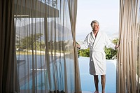 Middle aged man in robe pulling back poolside curtains (thumbnail)