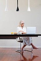 Middle aged woman sitting at table using laptop