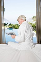 Middle aged man in robe sitting on bed reading newspaper with view out to swimming pool