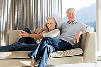 Middle aged couple reclining on couch (thumbnail)