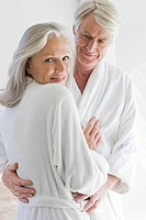 Middle aged couple in bathrobes hugging (thumbnail)