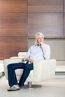 Thoughtful middle aged man sitting on modern armchair