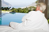 Middle aged man wearing bathrobe lying on bed and looking out at swimming pool