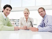 Smiling business people sitting at table (thumbnail)