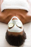 Woman wearing face mask and cucumber (thumbnail)