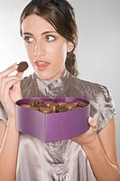 Woman sneakily eating a chocolate