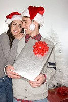 Festive couple with gift hugging
