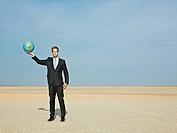 Man holding a globe in the desert