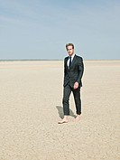 Businessman walking barefoot in the desert