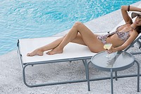 Glamorous woman on sunlounger by pool (thumbnail)
