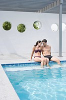 Couple on edge of swimming pool