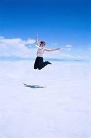 A woman jumping in a salt flat