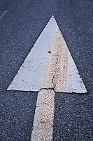 Arrow on road with tyre mark over it