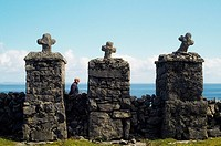 Inishmore, Aran Islands, Ireland, Man walking behind a stone wall topped with crosses