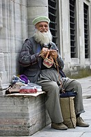 Man knitting outdoors in Asia