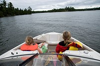 Lake of the Woods, Ontario, Canada, Girls sitting in front of boat