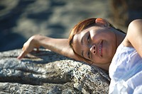 A woman resting on driftwood