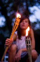 Young woman lighting a torch on the banks of the river Isar in the evening, Munich, Bavaria, Germany