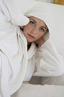 Young woman wearing bathrobe lying on a bed, Paris, Ile de France, France