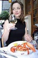 Young woman eating lobster in a restaurant, Paris, Ile de France, France