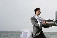 Young businessman on beach with paper blowing in face