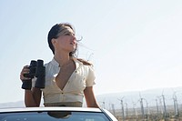 Young woman in convertible with binoculars