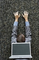 Young businessman reaching towards wall with laptop on back