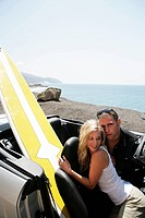 Portrait of young affectionate couple sitting in convertible with surfboard