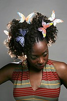 Portrait of young African American woman with butterflies in hair, studio shot