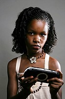 Portrait of young African American girl playing video game, studio shot
