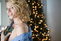 Portrait of sexy young woman holding small Christmas gift