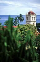 The church tower of the catholic mission behind treetops, Waikiri, Island of Taveuni, Fiji, South Seas, Oceania