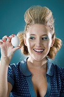 Cheerful young woman holding egg